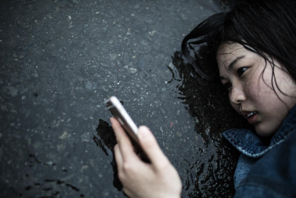 悲しそうに雨に打たれながらアスファルトに寝転がりスマホを見つめる女性
