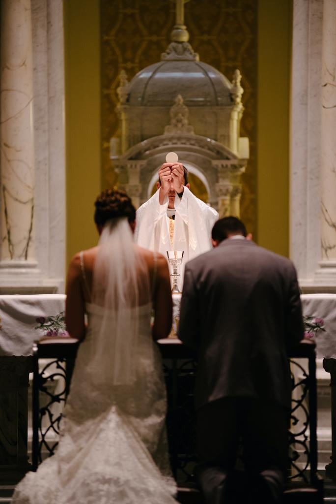 結婚式で神父の前で誓いを立てる新郎新婦