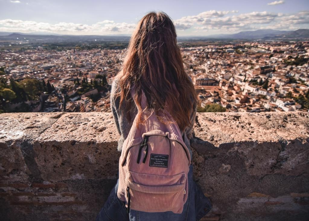 遠くの街を高台から眺める女性