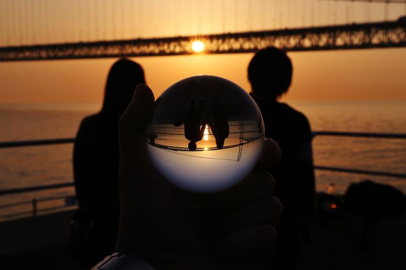 橋の向こうの夕暮れに沈む太陽と眺めるカップル