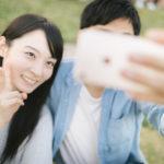 ピースサインをしながら自撮りをするカップル
