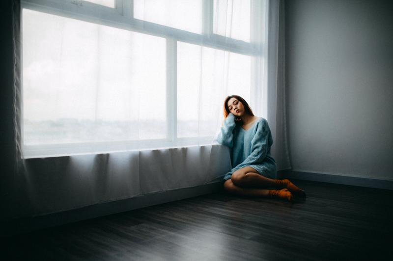 暗い部屋のなかで肘をつき座り込む女性