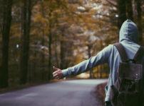 並木道でヒッチハイクするパーカー姿の男性