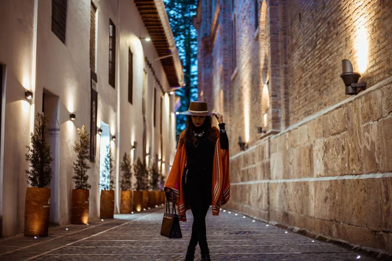 夜のお洒落な街並みでストローハットをつけてポーズをとる女性