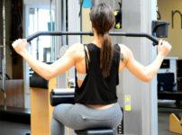 ジムのラットプルダウンマシンで身体を鍛える女性