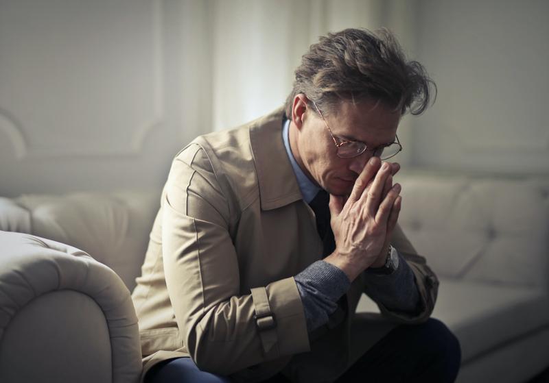 ソファに座り両肘を膝について思い悩むスーツスタイルの男性