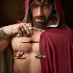 花と鎧が置かれた天秤を持つ筋肉質な男性