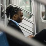 電車で一人座りながらつまらなそうにスマホをいじる男性