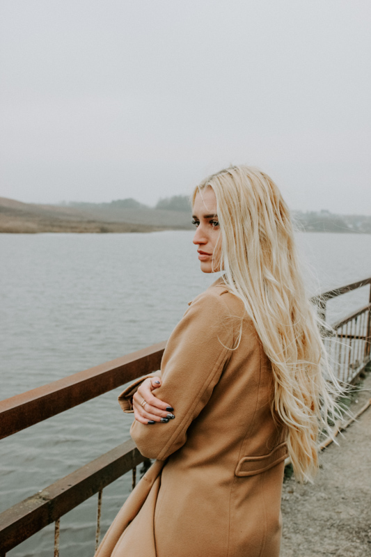 桟橋の上で自分の身体を抱きしめ遠くを眺める女性