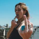 舌で指を舐めながら中指を立てて挑発する女性
