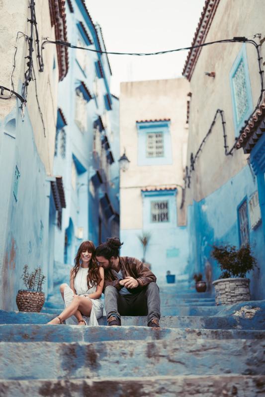仲良さそうに地中海風の街中の階段でくつろぐカップル