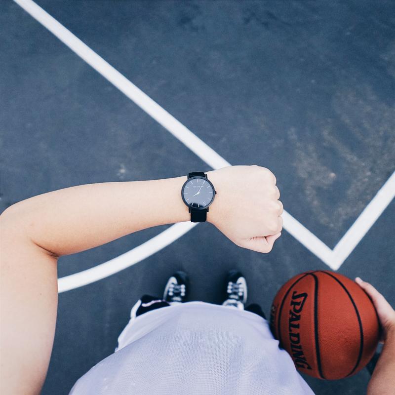 左腕に付けられた腕時計を見るバスケットボールプレイヤー