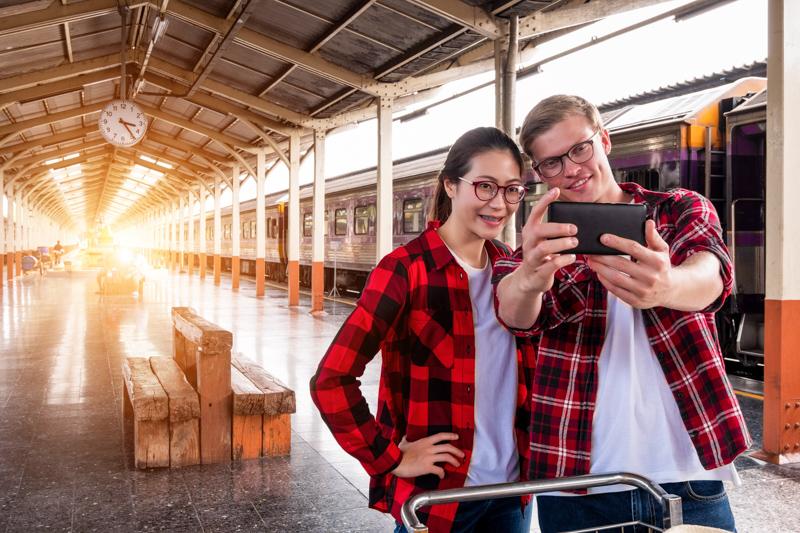 駅の構内で自撮りするペアルックのカップル