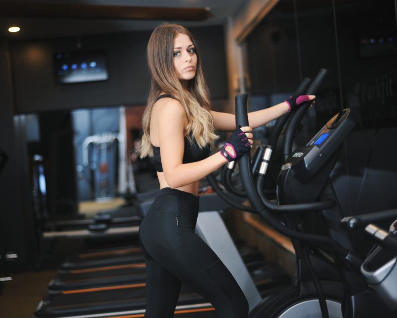 ジムで機械を使って身体を鍛える女性