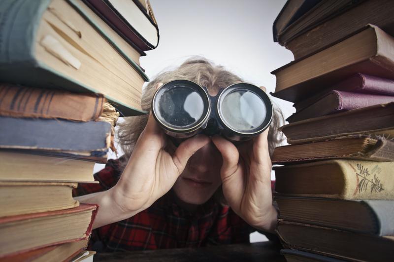 本に囲まれながら双眼鏡で覗き見る男性