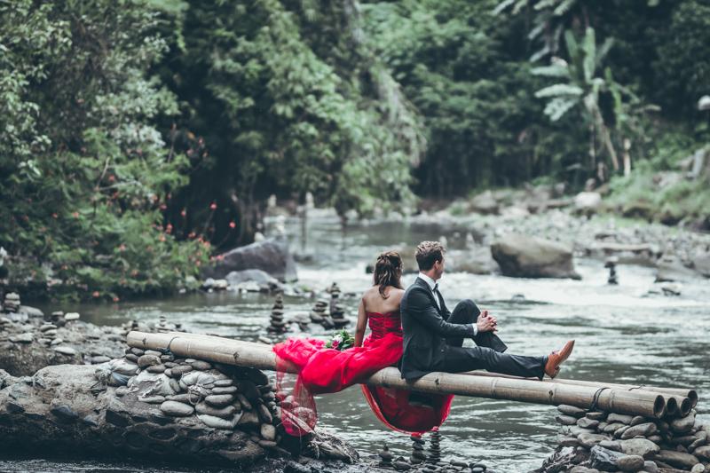 川にかかる小さな橋に背を付けて座るカップル
