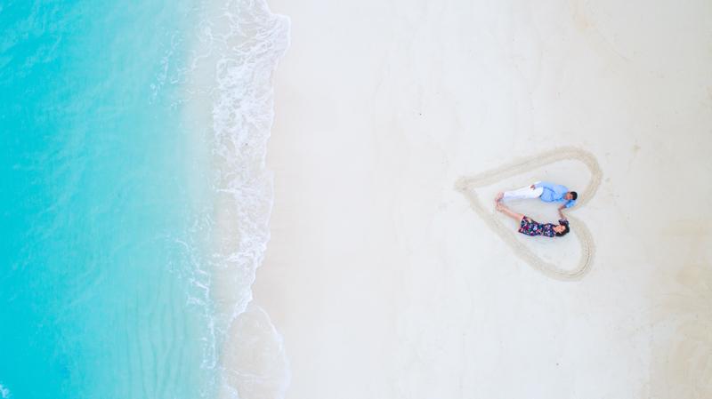 青く光る綺麗な砂浜でハートの中に寝転ぶカップル