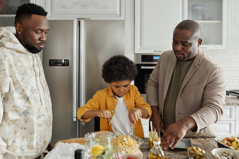 料理を作る二人の男性と子供