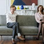 距離を置いてソファに座り険悪な雰囲気のカップル