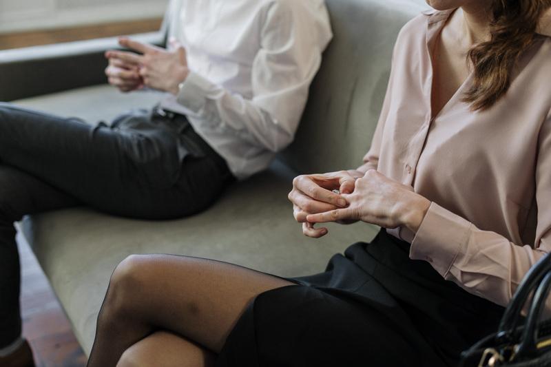 ソファに距離を置いて座り結婚指輪を取り外すカップル
