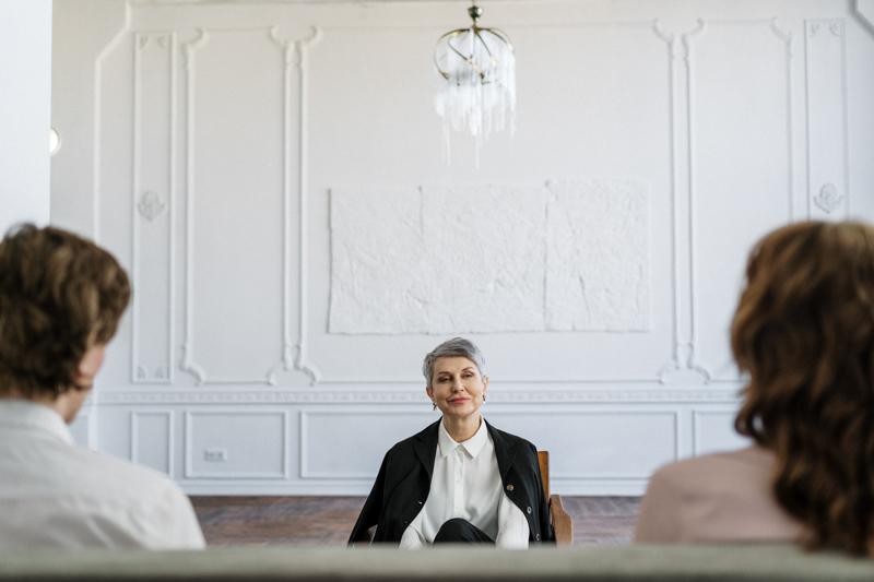 弁護士の女性と話す距離を置いてソファに座るカップル