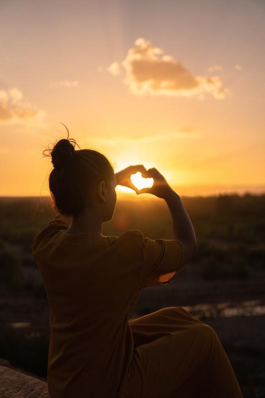 夕焼けの中ハートマークを手で形作る女性