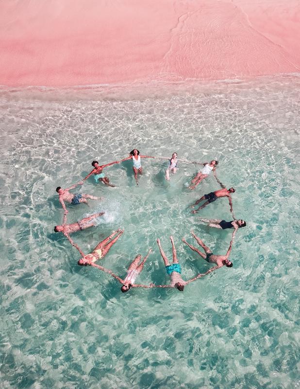 海に浮かびながら大きな輪を作る6組のカップル