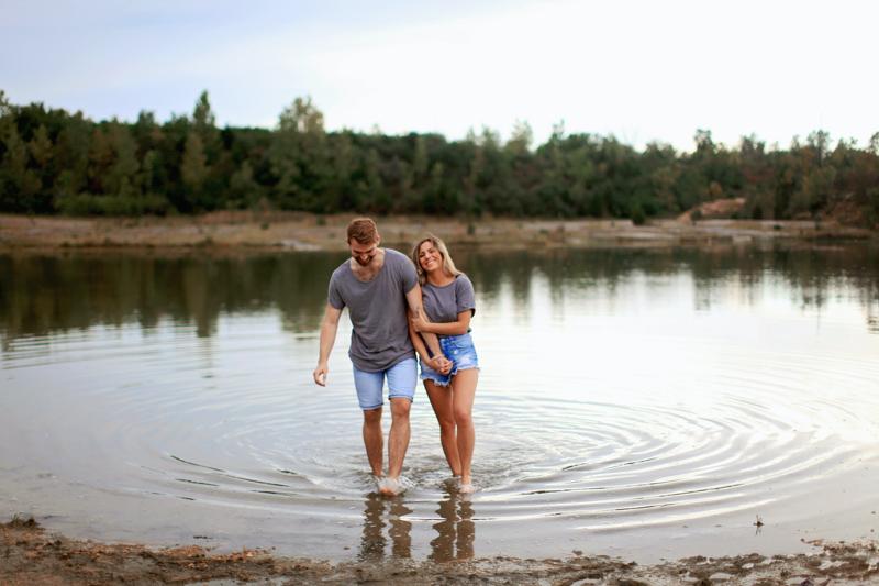 手を繋ぎ水辺で遊ぶカップル