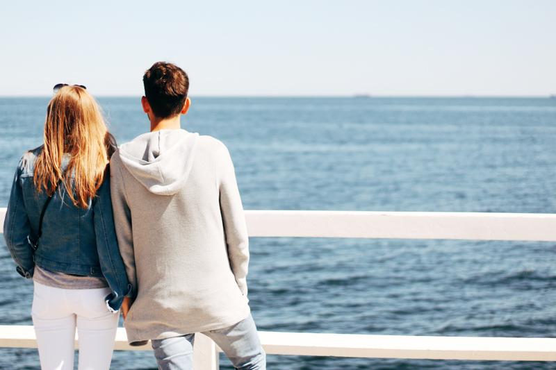 海を見ながら肩を寄せ合うカップル