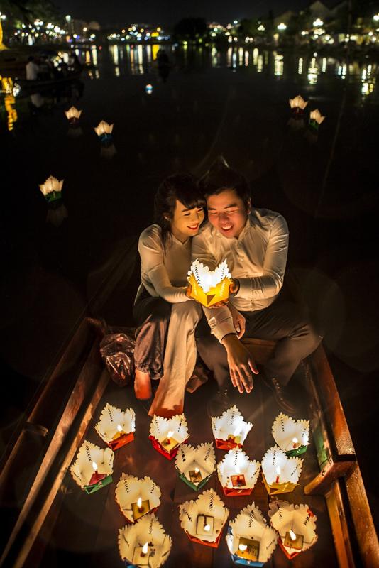 小さな船の上に灯された蝋燭を持ち笑顔で寄り添うカップル