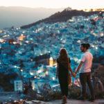 丘から綺麗な街並みを眺めるカップル