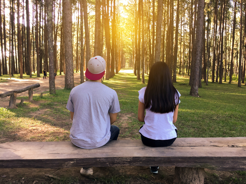 林の中のベンチで距離を置いて座る男女