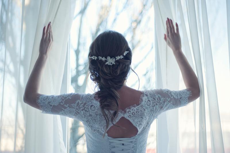 結婚式の朝カーテンを開けて窓の外を見る新婦