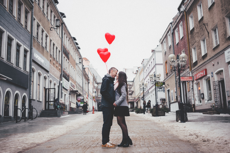 歩道でハートの形をした風船を持ちながら抱きしめ合うカップル