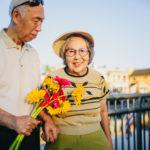 笑顔の妙齢の女性に花束を渡す男性