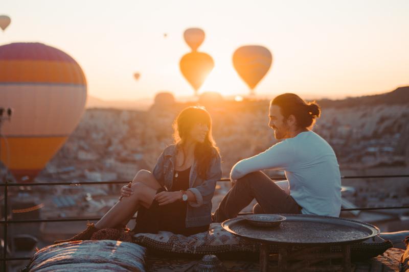 気球がたくさん浮かぶ夕方の丘の上で談笑するカップル